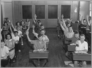 Children in a classroom with hands up facing the camera